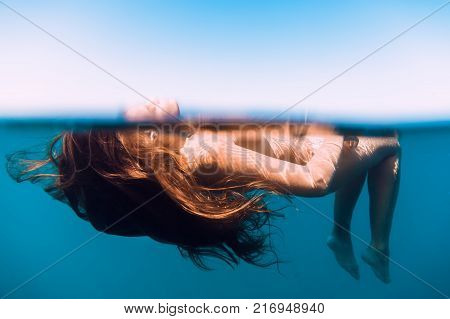 Red hair woman relaxed in ocean. Blue ocean in Bali