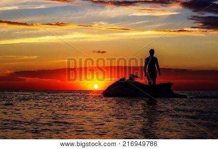silhouette of a man on a jet ski in the sun on the sea sunset in summer evening