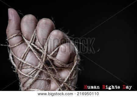 Woman hand tied with wire on dark background in low key. International human rights day concept.
