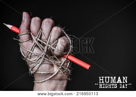Hand with red pencil tied with rope depicting the idea of freedom of the press or freedom of expression on dark background in low key. International human rights day concept.