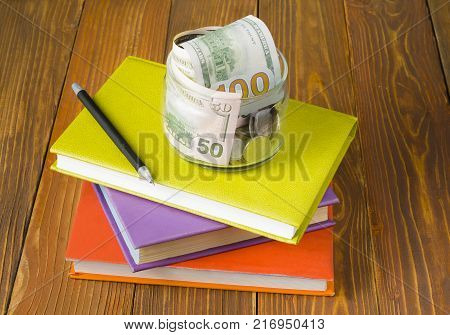 Money in glass jar.pen on stack of colorful books on wooden table.Concept of funding education.