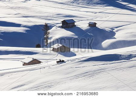 Wooden mountain chalets with a view on the Langkofel and Plattkofel, Sassolungo and Sassopiatto, dolomites mountains at the Alpe di Siusi or Seiser Alm in South Tyrol, Dolomites, Italy in winter.