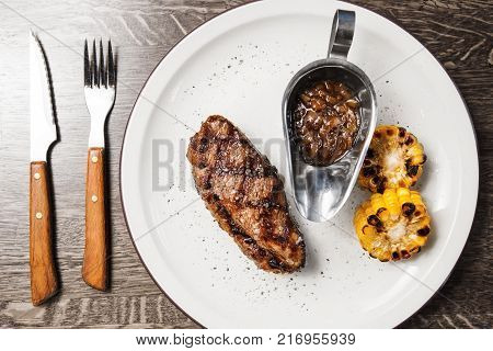 Beefsteak with grilled corn and sauce on white plate, closeup view on just prepared dish with meat and vegetables with fork and knife on napkin