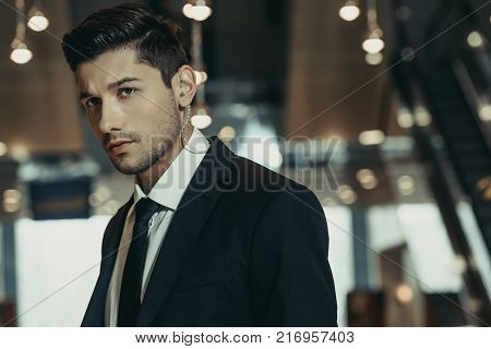 handsome security guard with security earpiece looking away