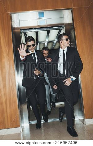 rear view of bodyguards and politician standing at elevator