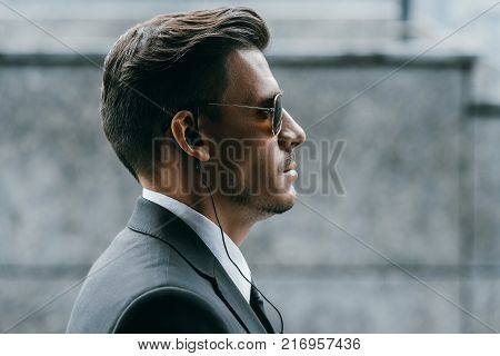 profile of handsome bodyguard with sunglasses and security earpiece