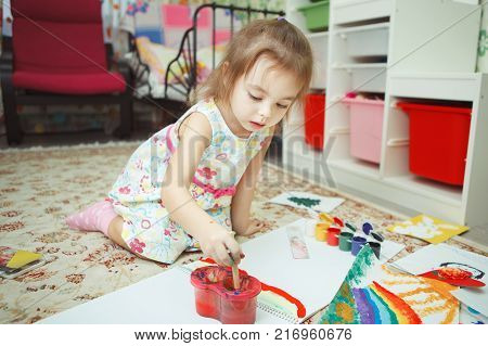 Young lady, wearing dress with floral pattern, girl sitting and drawing picture with gouache, brush and colorful paints, carpet on floor of cozy childrens room