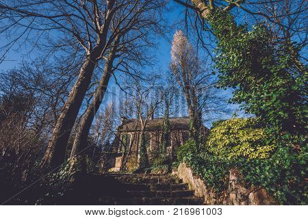 Saint Amandus chapel on Campo Santo historical cemetery in Sint-amandsberg municipality, Gent. Roman stone church, steps and ivy walls and trees in Ghent city, East Flanders, Belgium.