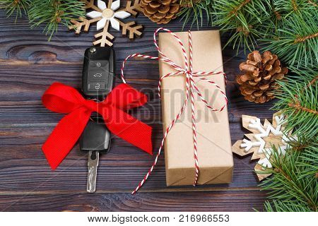 Car key with colorful bow with gift box and christmas decoration on wooden background.