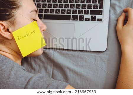 exhausted woman sleep on laptop with sticker on her cheek with deadline text on it