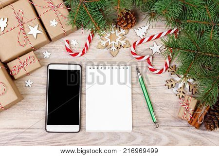 Christmas background with gift boxes mobile phone with back screen and blank notebook copy space. Template for new year goal or resolutions. Christmas mockup. Flat lay top view.