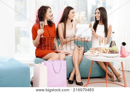 Pre-wedding care. Girls at a hen-party. They sit on the couch in a bright room with with a glass of champagne. Girl in veil.