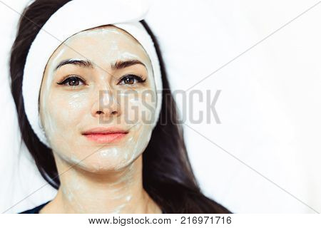 Beauty concept, beauty portrait of young woman applying cream on face, looking at camera and smiling. Head and shoulders of naturally beautiful woman touching face, studio, inside