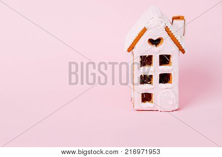 Pink and white icing gingerbread cookie house on pink background. Holiday real estate concept.