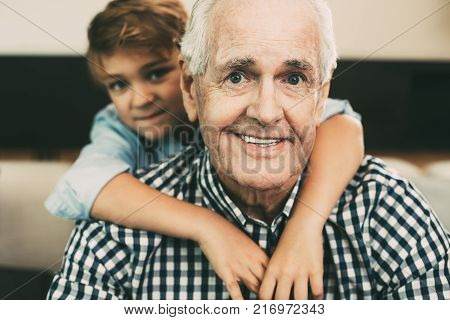 Portrait of little Caucasian grandson embracing happy grandfather, they looking at camera and smiling