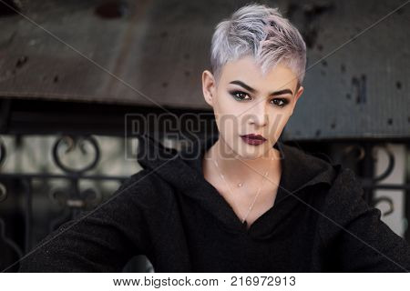 Young beautiful girl with short gray hair in a black jacket and aggressive leather boots, fashionable shooting on the street near the brick wall of the house
