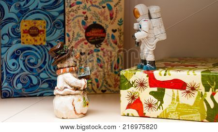 Christmas meeting with a snowman and an astronaut. Snowman in a hat and scarf. Astronaut in the spacesuit. In the hands of a snowman a small house.