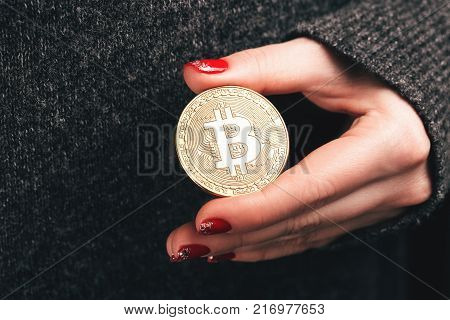 Bitcoin in woman's hand, closeup. Cryptocurrency investment concept.