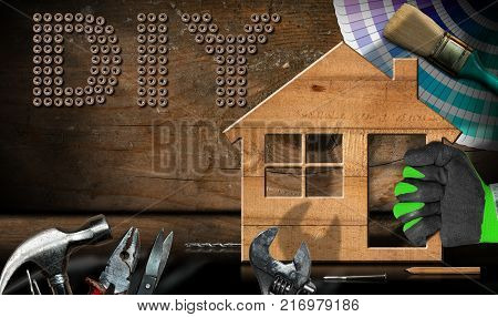 Screws in the shape of text Diy (Do it yourself) hand with work glove holding a wooden model house with work tools on a desk with reflections. Home improvement concept