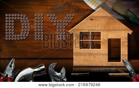 Screws in the shape of text Diy (Do it yourself) wooden model house with work tools on a desk with reflections. Home improvement concept