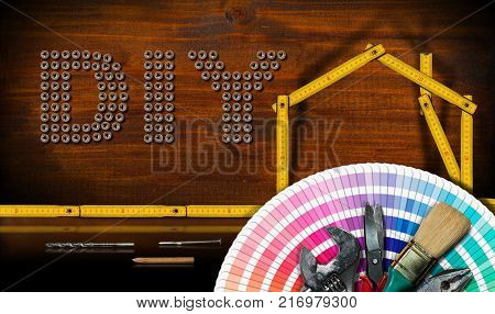 Screws in the shape of text Diy (Do it yourself) wooden folding ruler in the shape of a house with work tools - Home improvement concept