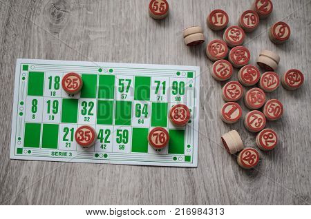 Developing bingo table game old lotto game with wooden elements and cards bingo on a wooden background.