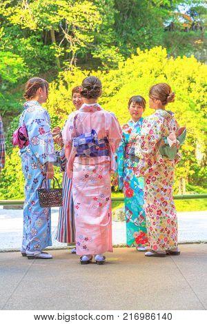 Kamakura, Japan - April 23, 2017: five Japanese women in zen garden of stone and sand, dressed with classic pink kimonos at Takera Hokoku-ji Temple of Kamakura. Vertical shot. Hanami spring season.