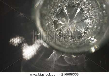 transparent faceted glass with bubbly water in the sun refracted light