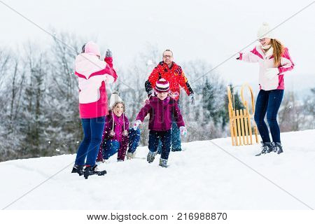 Family with kids having fun witn snowball fight in winter