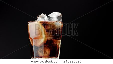 Cocktail with cola and limes slices isolated on blackbackground