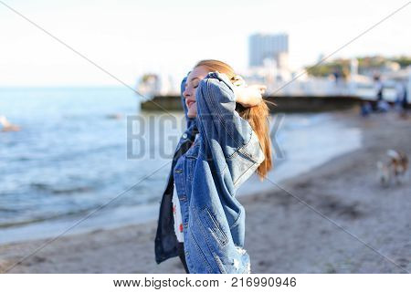 Attractive young woman with smile on face turns head to sides and develops beautiful hair, turns in profile and poses on sea shore against blue sky on clear summer day. Woman of European appearance with blond mid-length hair dressed in blue denim jacket.