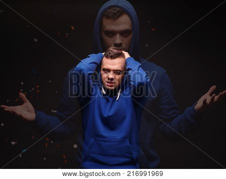The guy a drug addict clings to his head after using the drug is in euphoria on a black background