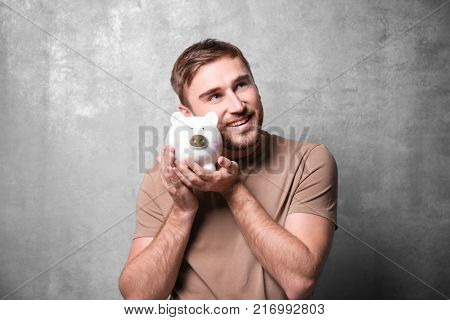 Young man with piggy bank on grunge background