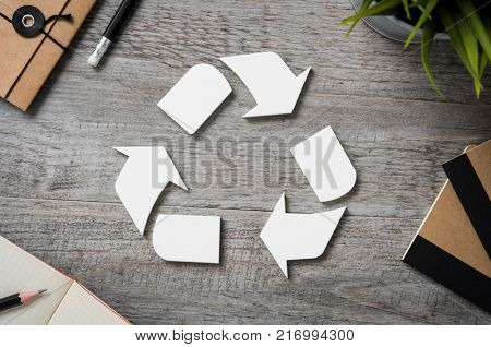 Top view of recycle sign on vintage wooden table with office equipment. High angle view of recycle logo with recycled paper and notepad on business desk. Recycling symbol and environmental concept.