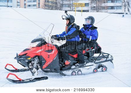 Rovaniemi Finland - March 2 2017: People with selfie stick riding a snowmobile on the frozen lake in winter Rovaniemi Lapland Finland