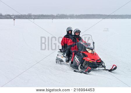 Rovaniemi Finland - March 2 2017: People riding a snowmobile in the frozen lake in winter Rovaniemi Lapland Finland