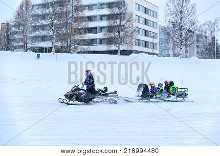 Rovaniemi Finland - March 2 2017: Man riding a snowmobile with kids on the frozen lake in winter Rovaniemi Lapland Finland