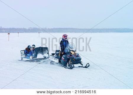 Rovaniemi Finland - March 2 2017: Man riding a snowmobile with kids in the frozen lake in winter Rovaniemi in Lapland Finland