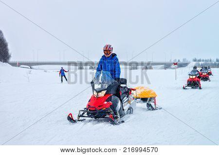 Rovaniemi Finland - March 2 2017: Man riding a snowmobile on the frozen lake at winter Rovaniemi Lapland Finland