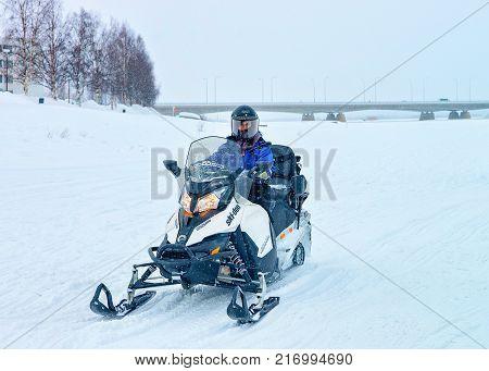 Rovaniemi Finland - March 2 2017: Man riding a snowmobile in the frozen lake in winter Rovaniemi Lapland Finland