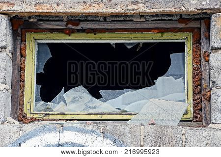 a small window with broken pieces of glass on a brick building