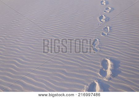 Footprints from wind and feet of people left on snow-white sand in deserted hot sandy desert on sunny day. Concept of wildlife and environment, sandy desert, hot country and travel.