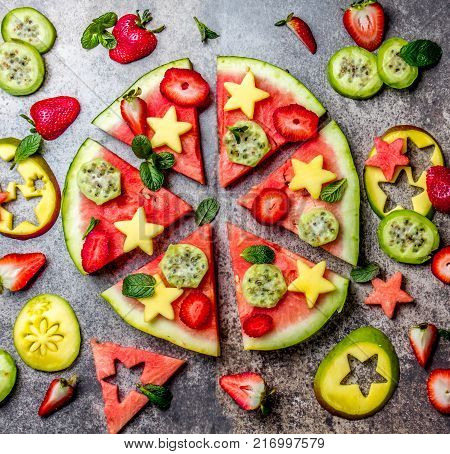 Fruit watermelon pizza with tropical fruits and berries - mango, tuna and mint on stone gray background. Pizza made of watermelon and fruits, top view.