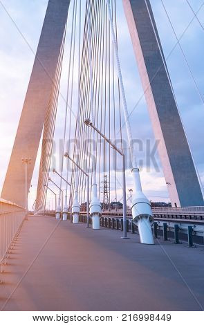 Highway going through a cable-stayed bridge with big steel cables, close-up in the evening during a sunset against a background of blue sky and clouds