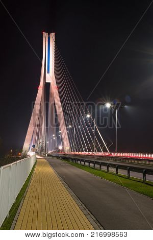 Highway going through a cable-stayed bridge with big steel cables, close-up in the night