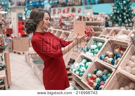 Cheerful happy customer girl choosing gifts for Christmas and New Year. She is taking red Christmas tree decorations. difficult decision. Various choice