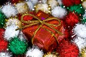 Christmas gift rests in a pool of colored tensile balls waiting for Santa poster