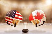 Low angle view of hockey helmets with Canada and USA flags painted and hockey puck on ice in brightly lit stadium background. Concept of intense rivalry between the two hockey nations. poster