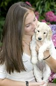Cute Brunette holding a golden labradoodle puppy and giving it a kiss poster