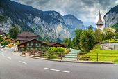 Famous stunning touristic town with high cliffs in background, Lauterbrunnen, Bernese Oberland, Switzerland, Europe poster
